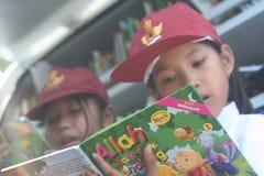 istruisca gli studenti che leggono un libro nella biblioteca mobile Immagini Stock