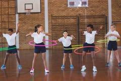 Istruisca i bambini che giocano con il hula-hoop dentro nel campo da pallacanestro Immagine Stock Libera da Diritti