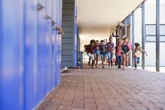 Istruisca i bambini che si dirigono alla macchina fotografica nel corridoio della scuola elementare fotografie stock