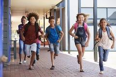 Istruisca i bambini che si dirigono nel corridoio della scuola elementare, vista frontale fotografia stock