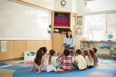 Istruisca i bambini che si siedono sul pavimento riunito intorno all'insegnante fotografie stock libere da diritti