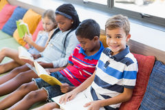 Istruisca i bambini che si siedono sul sofà e sul libro di lettura in biblioteca Immagine Stock Libera da Diritti