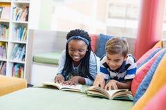 Istruisca i bambini che si trovano sul sofà e sul libro di lettura Immagini Stock Libere da Diritti