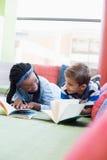 Istruisca i bambini che si trovano sul sofà e sul libro di lettura Immagine Stock