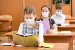 Istruisca i bambini con la maschera della protezione contro il virus di influenza alla lezione Immagini Stock