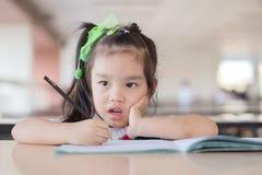 istruisca il bambino che pensa alla risposta che si siede al suo scrittorio Immagine Stock