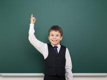 Istruisca il ragazzo dello studente che posa alla lavagna pulita, mostri il dito su ed indichi, fare smorfie ed emozioni, vestiti fotografia stock