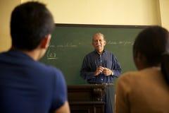 Istruisca la gente, professore che parla con studenti durante la lezione in co Fotografia Stock