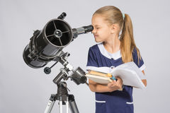 Istruisca la ragazza che guarda tramite un telescopio che sta con i manuali Fotografie Stock Libere da Diritti