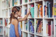 Istruisca la ragazza che prende un libro dallo scaffale per libri in biblioteca Fotografia Stock Libera da Diritti