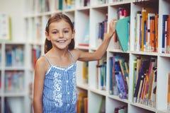 Istruisca la ragazza che prende un libro dallo scaffale per libri in biblioteca Fotografie Stock Libere da Diritti
