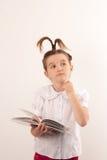 Istruisca la ragazza con stile di capelli divertente che legge un libro fotografia stock libera da diritti