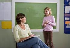 Istruisca la ragazza e l'insegnante dalla lavagna in aula Immagini Stock