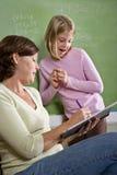 Istruisca la ragazza e l'insegnante dalla lavagna in aula Fotografie Stock Libere da Diritti