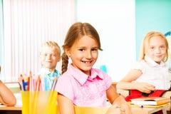 Istruisca la ragazza ed altri allievi che si siedono agli scrittori Fotografia Stock