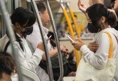 Istruisca la ragazza nel Giappone si è vestito in uniforme scolastico e maschera chirurgica sul modo alla scuola fotografia stock