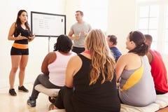Istruttore Addressing Overweight People di forma fisica al club di dieta fotografia stock libera da diritti