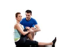 Istruttore aerobico dell'uomo che posiziona allenamento della donna Fotografia Stock