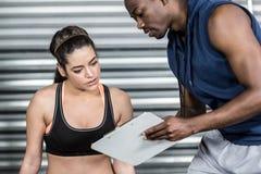 Istruttore atletico che spiega piano di allenamento alla donna Fotografia Stock