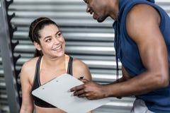 Istruttore atletico che spiega piano di allenamento alla donna Immagine Stock