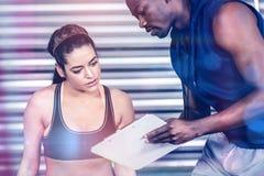 Istruttore atletico che spiega piano di allenamento alla donna Immagini Stock Libere da Diritti