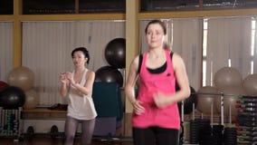 Istruttore atletico della donna che fa classe aerobica con gli steppers al gruppo della gente su un centro di forma fisica Concet stock footage