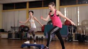 Istruttore atletico della donna che fa classe aerobica con gli steppers al gruppo della gente su un centro di forma fisica Concet video d archivio