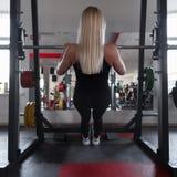 Istruttore atletico di una giovane donna in abiti sportivi neri in scarpe da tennis della palestra Ragazza che fa gli esercizi in fotografie stock