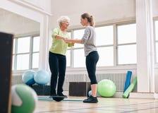 Istruttore che aiuta donna senior sulla piattaforma di addestramento dell'equilibrio di bosu Immagini Stock