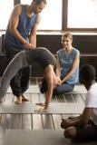 Istruttore che aiuta donna sportiva adatta che si esercita del ponte, Immagini Stock Libere da Diritti