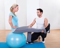 Istruttore che aiuta una donna con gli esercizi dei pilates Fotografia Stock Libera da Diritti