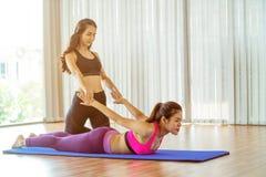 Istruttore che assiste donna sull'allungamento del corpo Immagini Stock