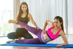 Istruttore che assiste donna sull'allungamento del corpo Fotografia Stock Libera da Diritti