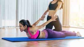 Istruttore che assiste donna sull'allungamento del corpo Fotografie Stock