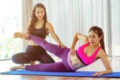 Istruttore che assiste donna sull'allungamento del corpo Fotografia Stock