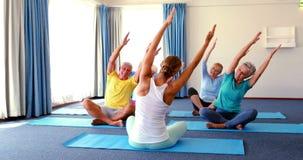 Istruttore che assiste gli anziani nell'yoga di pratica stock footage