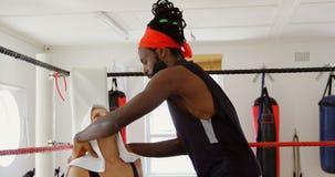 Istruttore che dà massaggio al pugile femminile in ring 4k video d archivio
