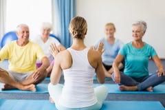 Istruttore che esegue yoga con gli anziani fotografia stock