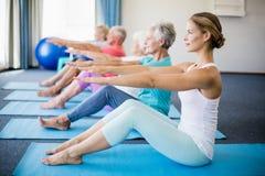 Istruttore che esegue yoga con gli anziani immagine stock
