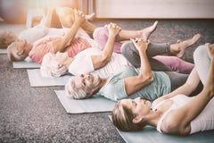 Istruttore che esegue yoga con gli anziani immagini stock