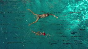 Istruttore che insegna ad un nuoto della ragazza in uno stagno stock footage