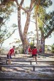Istruttore che istruisce i bambini durante l'addestramento di corsa ad ostacoli fotografia stock