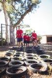 Istruttore che istruisce i bambini durante l'addestramento di corsa ad ostacoli dei pneumatici immagine stock
