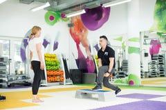 Istruttore che mostra esercizio dei pesi Immagine Stock