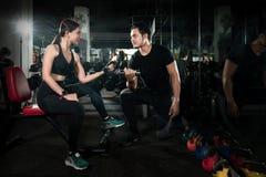 Istruttore che si esercita con il suo cliente alla palestra, donna d'aiuto di forma fisica dell'istruttore personale che lavora c immagini stock