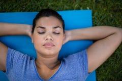 Istruttore con gli occhi chiusi che riposano sulla stuoia di esercizio Immagine Stock Libera da Diritti