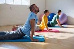 Istruttore con gli studenti che praticano posa della cobra nello studio di yoga Immagine Stock