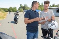 Istruttore della motocicletta che mostra carta allo studente Fotografia Stock Libera da Diritti