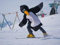 Istruttore dello sci della scuola dello sci per i bambini in un vestito di pinguino Corsa con gli sci, stagione invernale Fotografia Stock Libera da Diritti