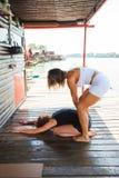 Istruttore di forma fisica che assiste giovane donna nell'allungamento dell'esercizio Immagine Stock